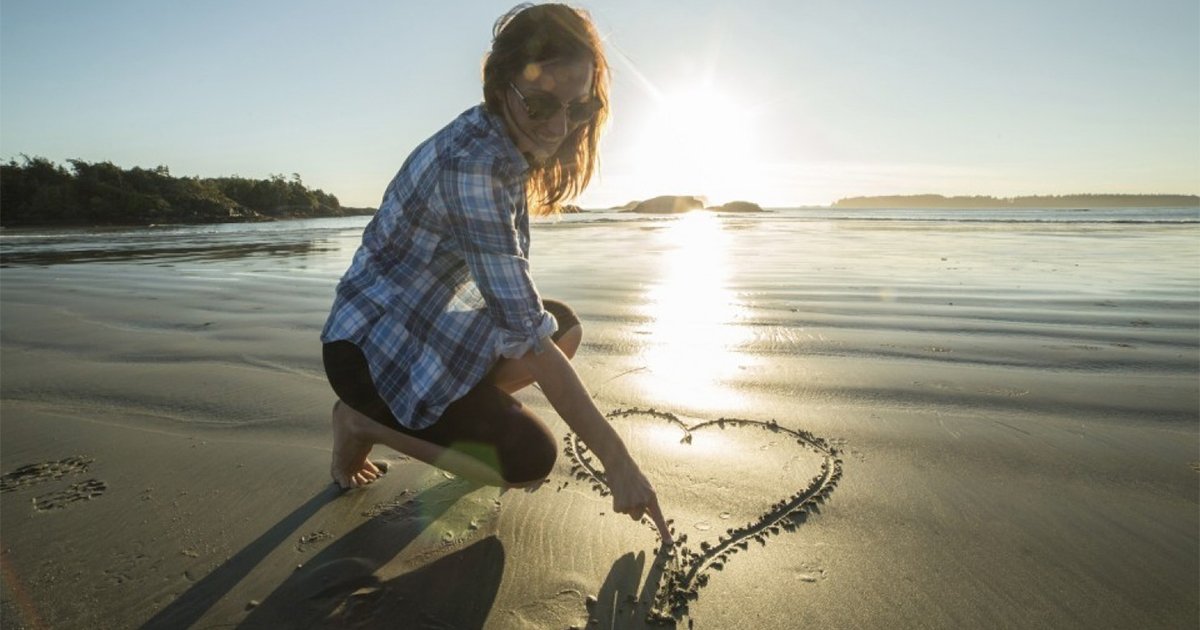 woman draws heart in sand