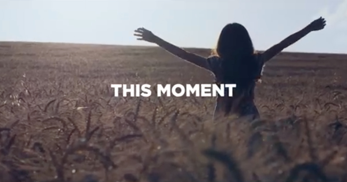 "Young girl in field with ""this moment"" supered"